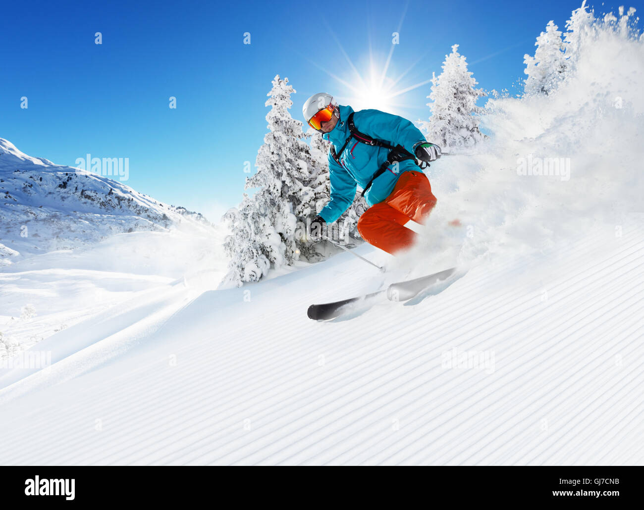 Skier on piste running downhill in beautiful Alpine landscape. Blue sky on background. Free space for text - Stock Image