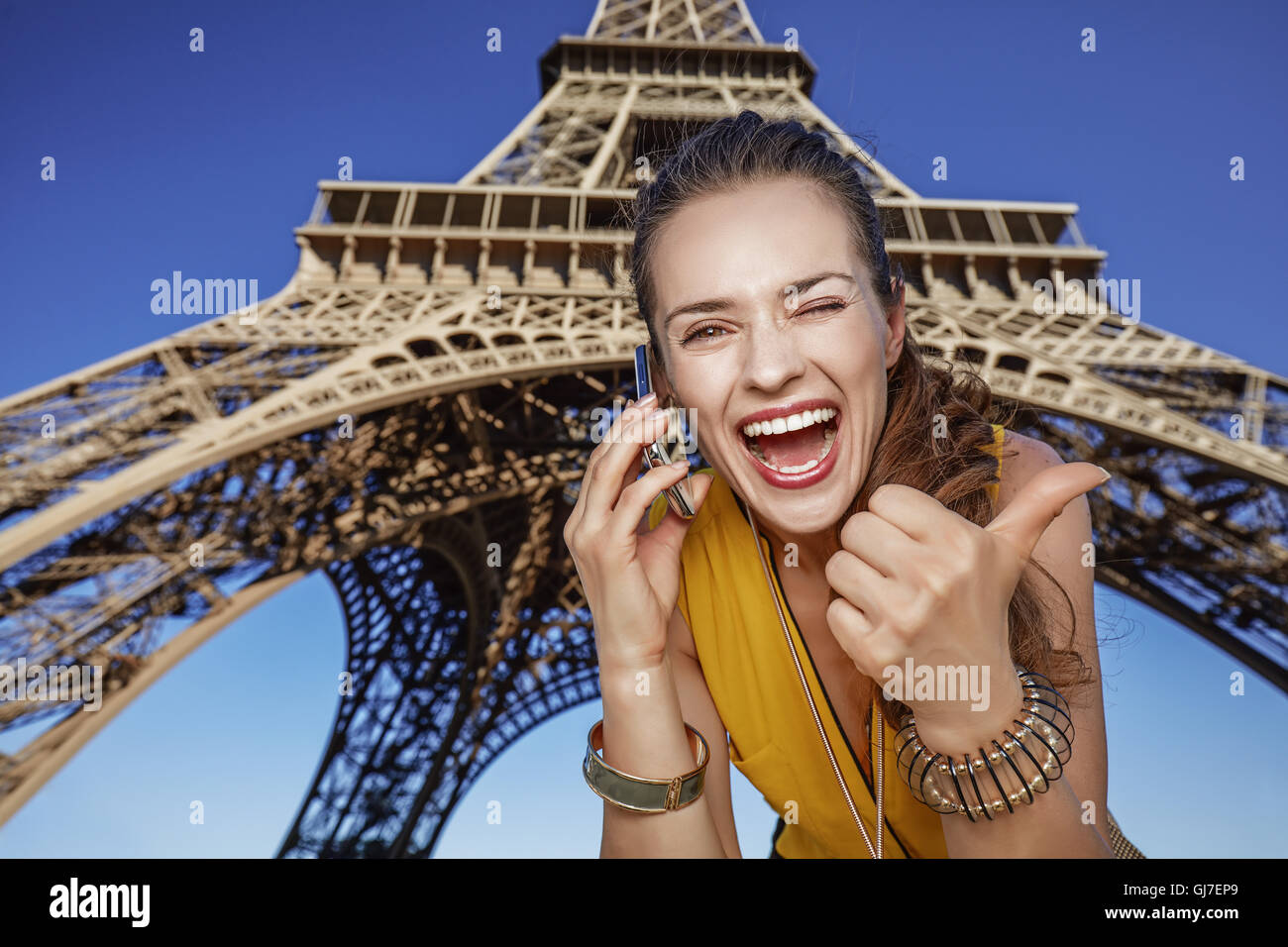 Touristy, without doubt, but yet so fun. happy young woman showing thumbs up and speaking on a mobile phone against - Stock Image