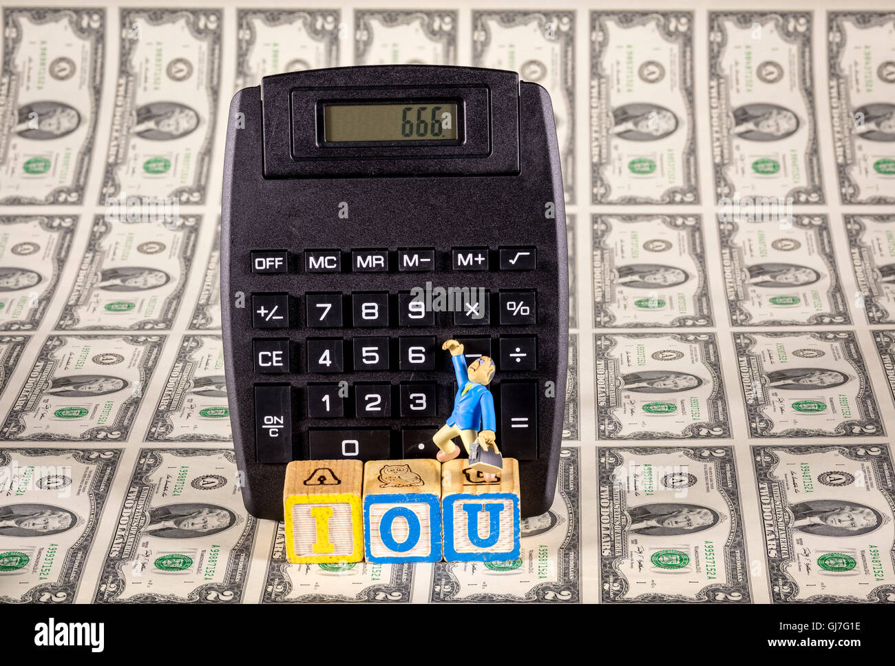 Figure of a man with money and a calculator with the letters IOU - Stock Image