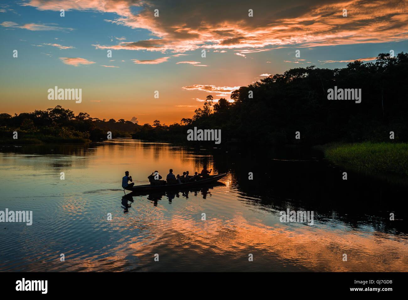 A canoe with tourists paddling over Amazon at sunset. Yasuni National Park, Ecuador, South America. - Stock Image