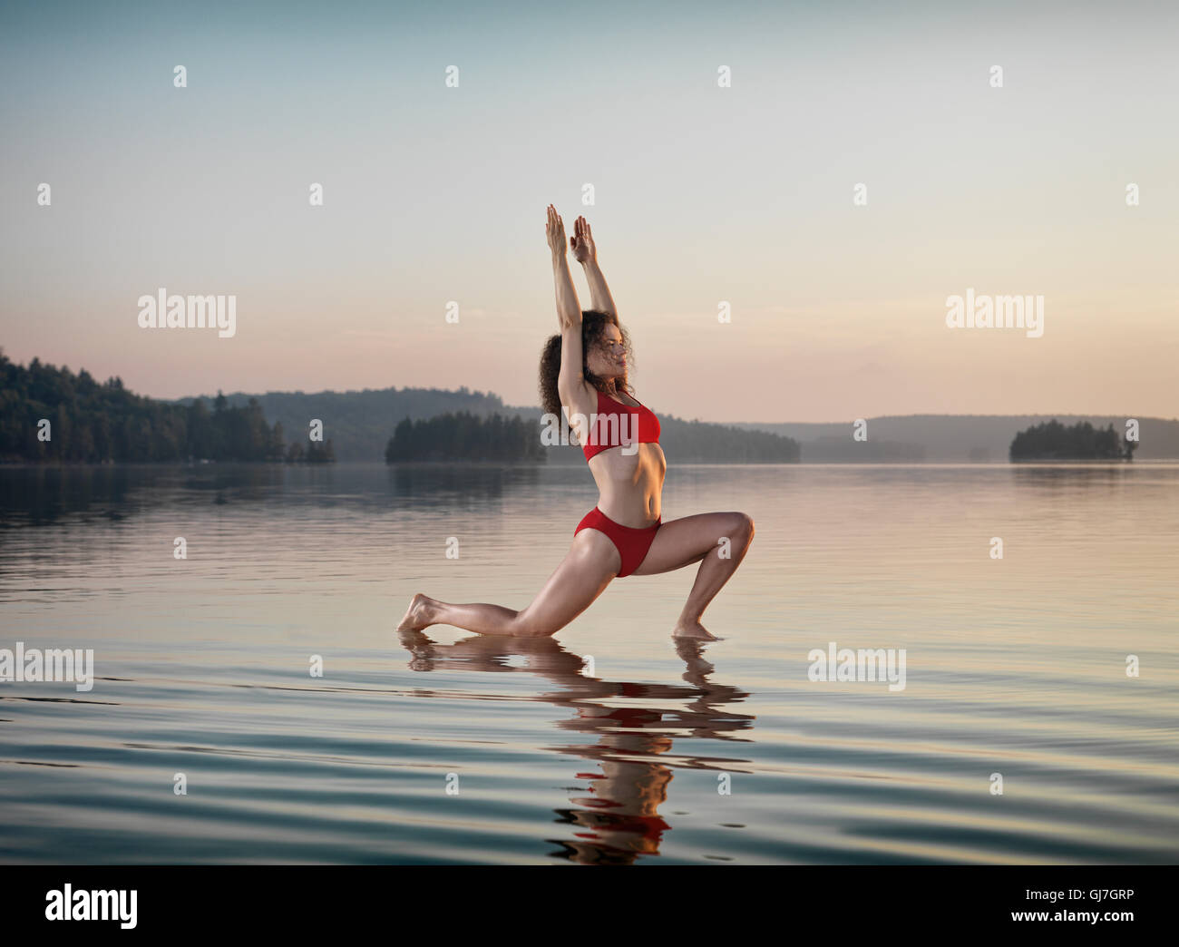 Young woman practicing Hatha yoga Low Lunge on a floating platform in water on the lake during misty sunrise in - Stock Image