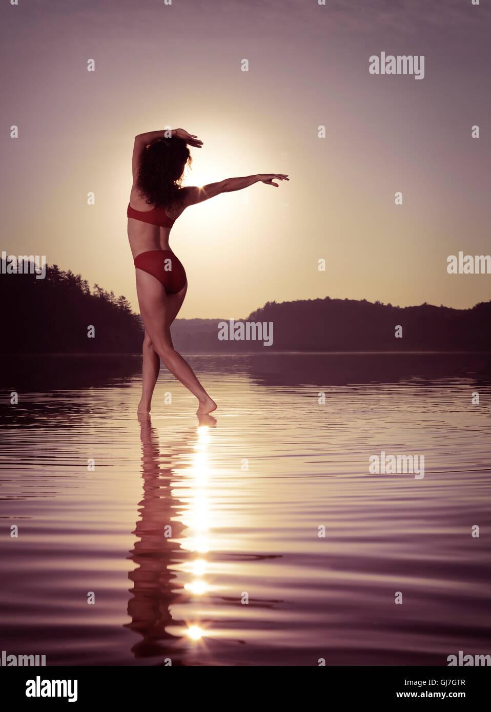 Young woman in swimsuit dancing in the sun on the water in beautiful morning sunrise scenery. Muskoka, Ontario, - Stock Image