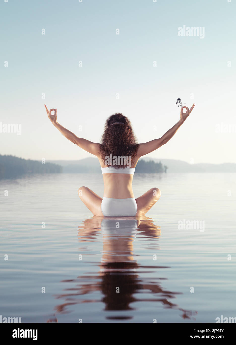 Artistic concept of a woman meditating with a butterfly on her hand. Practicing meditation on a floating platform - Stock Image