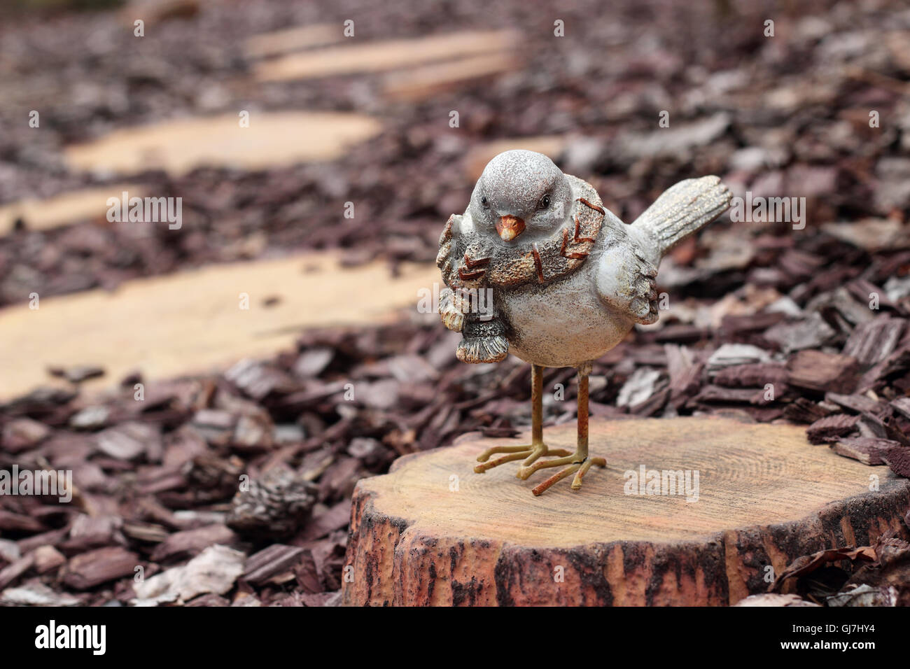 Figurines - Bird on a stub on a wooden stub background - Stock Image