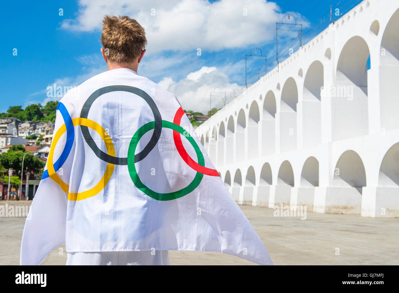 RIO DE JANEIRO - MARCH 06, 2015: Athlete draped with Olympic flag stands outdoors in the plaza at the famous Lapa - Stock Image