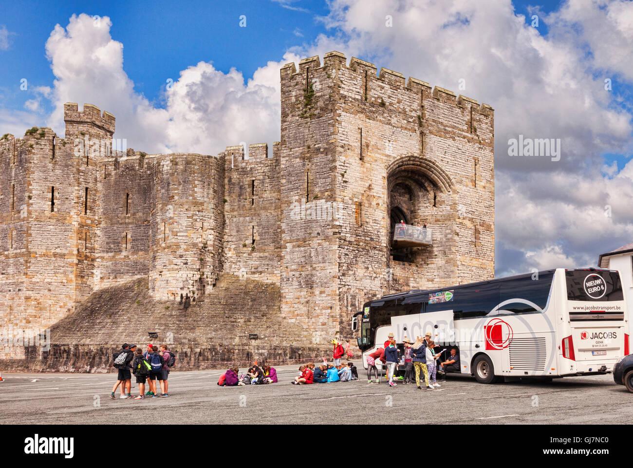 Tourists and tour coach at Caernarfon Castle, Gwynedd, Wales, UK - Stock Image