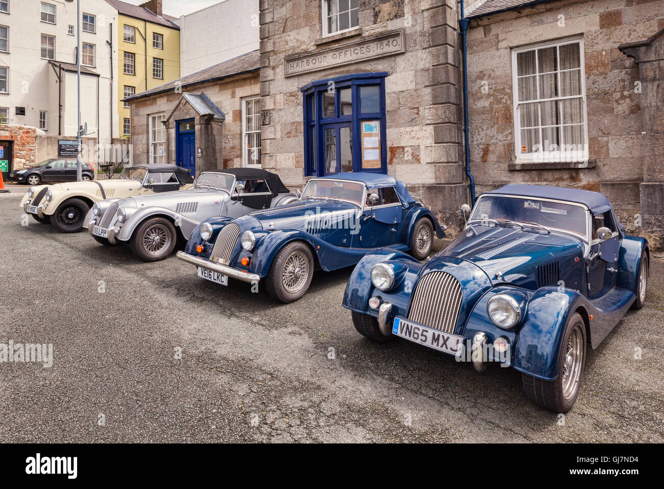 Four Morgan sports cars lined up in front of the Harbour Offices, Caernarfon, Wales, UK - Stock Image