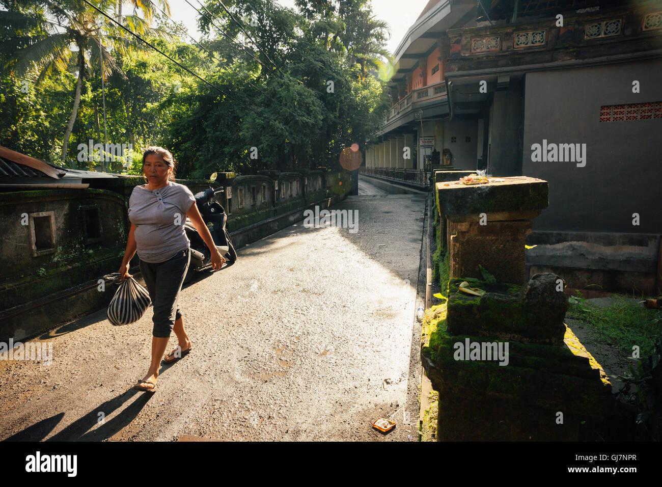 Ubud, Indonesia - February 28, 2016: Woman crossing old stone bridge in the morning hour, Ubud, Bali, Indonesia. - Stock Image