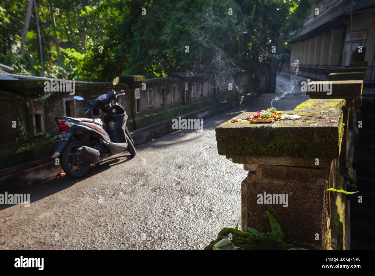 Burning offerings on the old mossy bridge in the morning hour, Ubud, Bali, Indonesia. - Stock Image