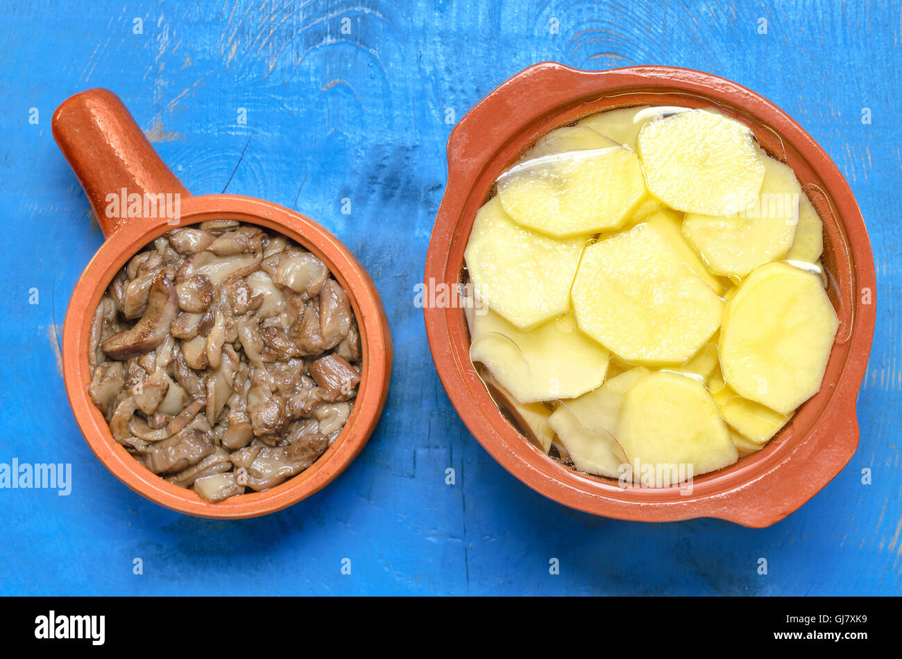 Fried mushrooms and raw chopped potatoes Stock Photo
