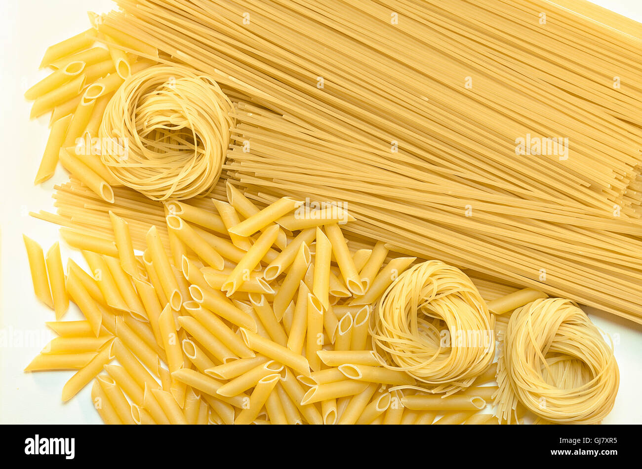 Different pasta lying on the white surface - Stock Image