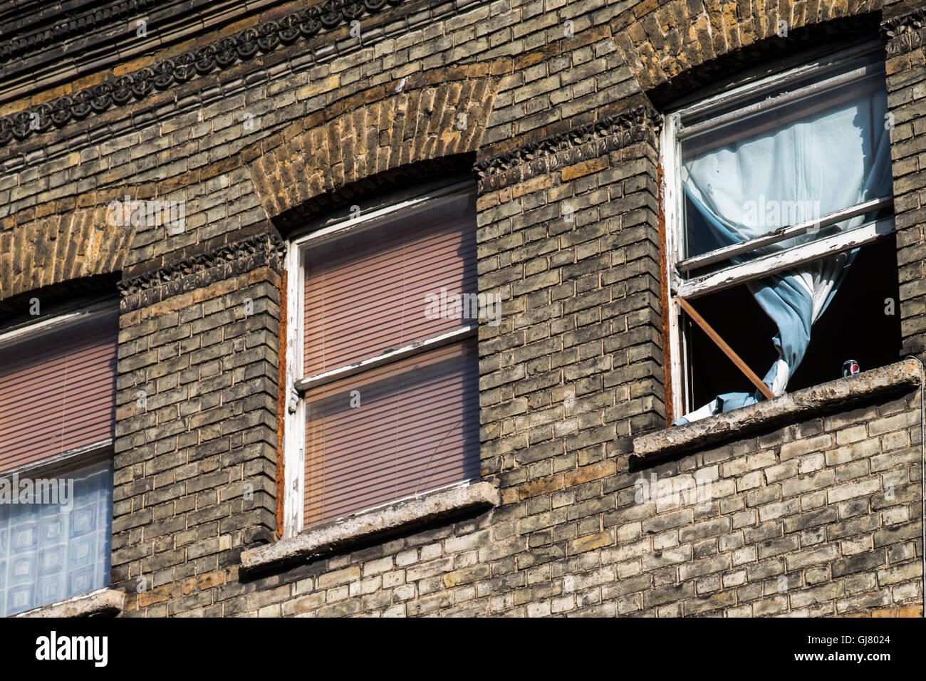 Row of Victorian Hatch Windows, London.  One window is wedged open with a piece of wood. - Stock Image