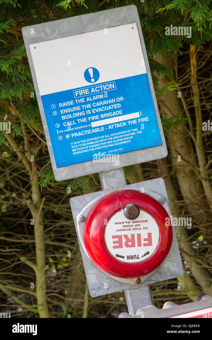Old Fashioned Fire Alarm Warning Bell with Fire Action Notice - Stock Image