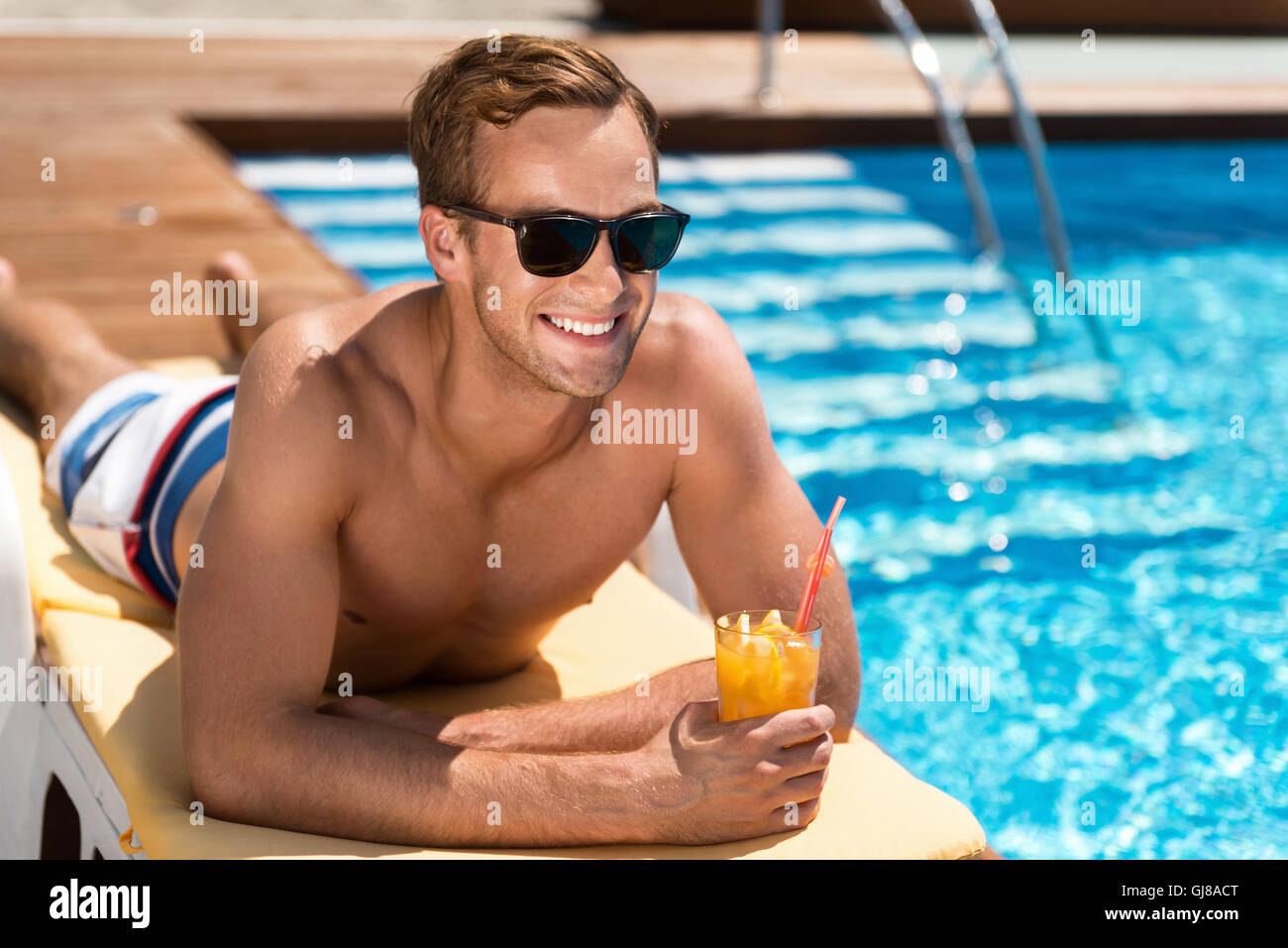 Positive handsome man lying on the sunbed - Stock Image