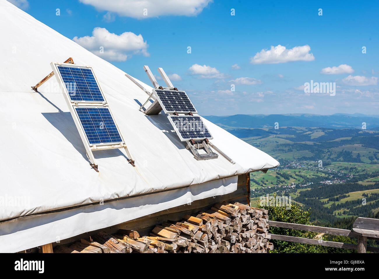 Portable solar panels on the roof of a house in the mountains. Stock Photo