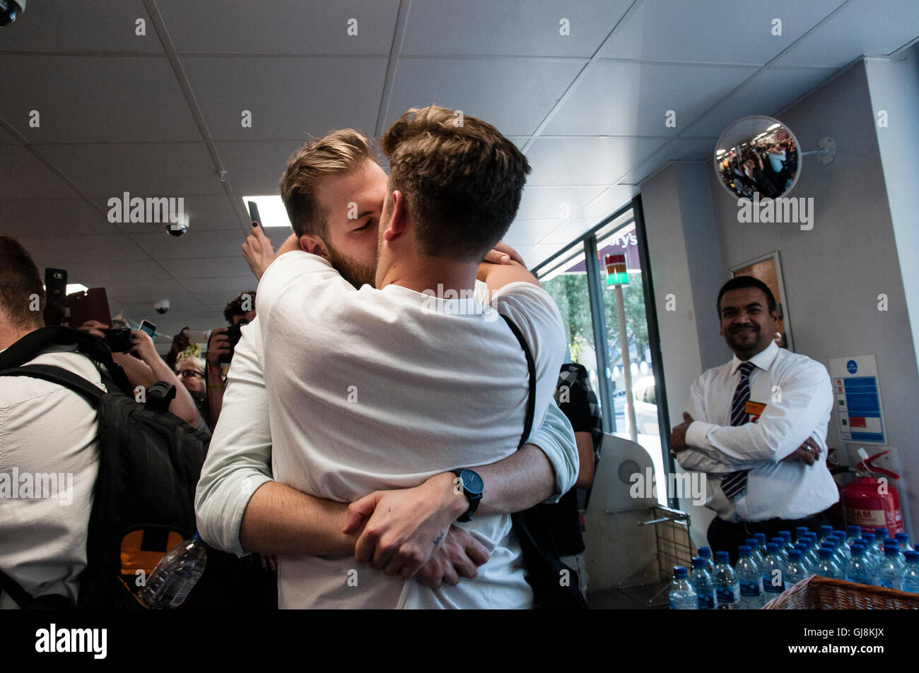 A couple kissing in a supermarket. A group of people hold a 'Big Kiss' protest for a homophobic incident - Stock Image