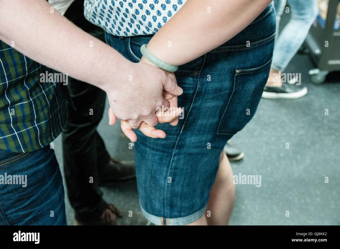 A couple holding hands. A group of people hold a 'Big Kiss' protest for a homophobic incident happened last - Stock Image