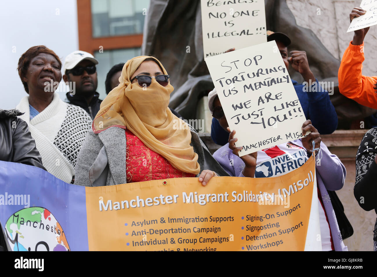 Manchester, UK. 13th Aug, 2016. A women holds up a banner representing Manchester Migrant Solidarity Campaign in - Stock Image