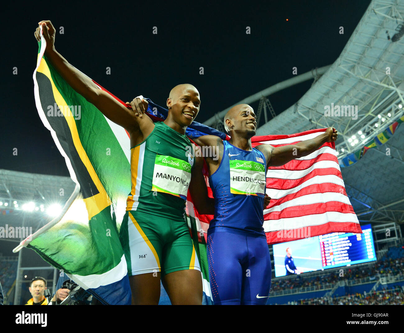 RIO DE JANEIRO, BRAZIL - AUGUST 13: Luvo Manyonga of South Africa and Jeff Henderson of the USA hold their national - Stock Image