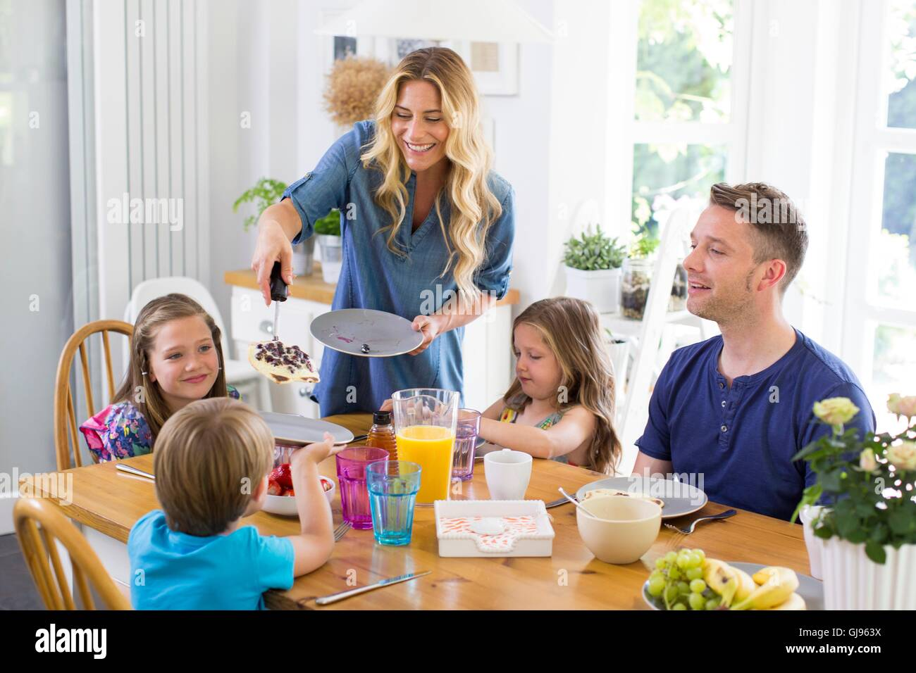 PROPERTY RELEASED. MODEL RELEASED. Family at dining table having a meal. - Stock Image