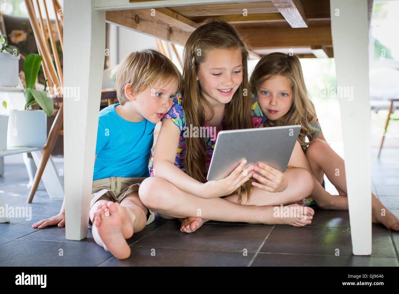 PROPERTY RELEASED. MODEL RELEASED. Three siblings under table with digital tablet. - Stock Image