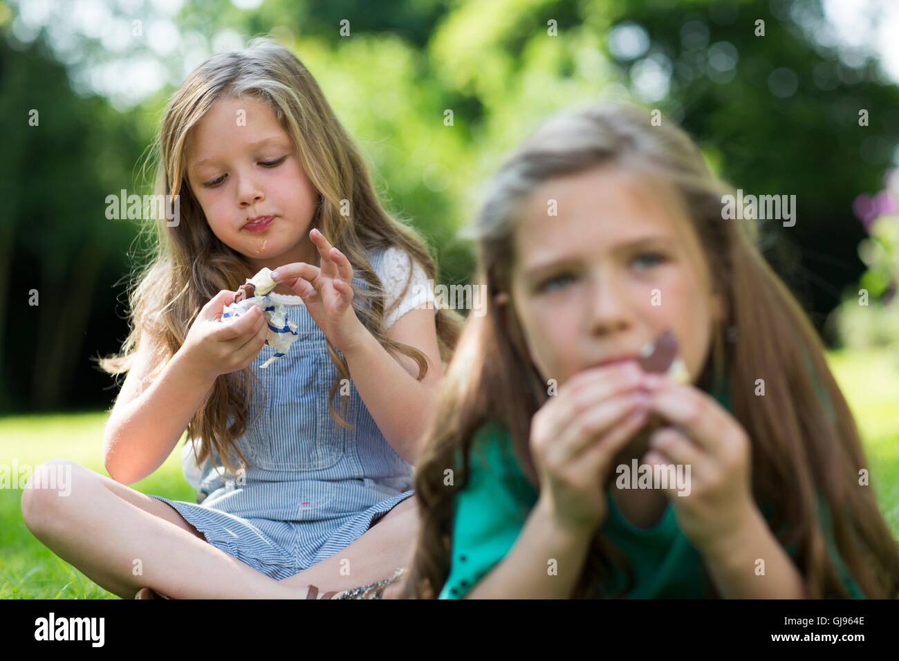 PROPERTY RELEASED. MODEL RELEASED. Girls eating ice-creams in the garden. - Stock Image