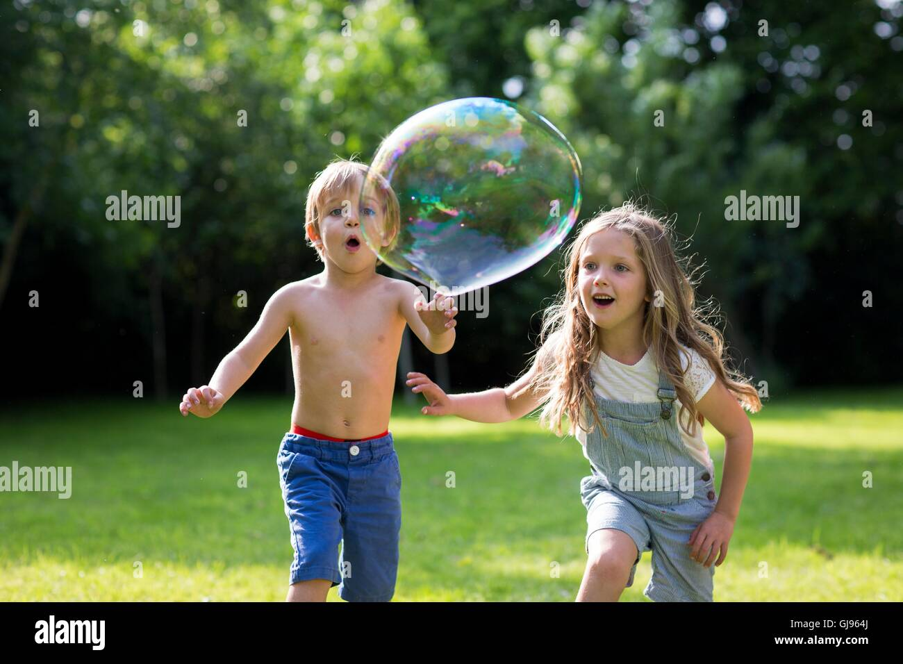 PROPERTY RELEASED. MODEL RELEASED. Brother and sister chasing bubbles in garden. - Stock Image