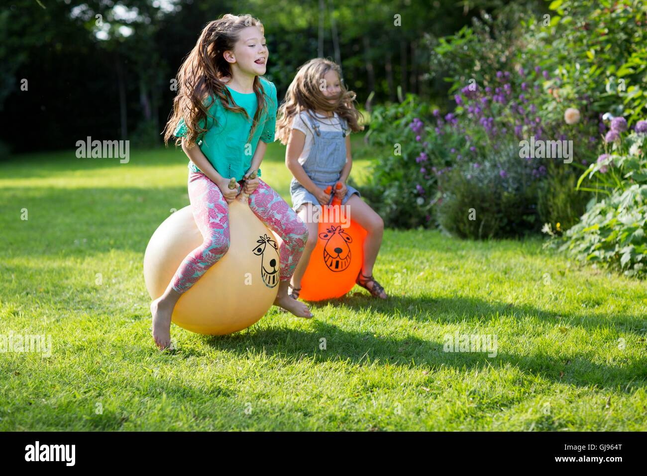PROPERTY RELEASED. MODEL RELEASED. Two sisters bouncing on bouncy hoppers in the garden. - Stock Image