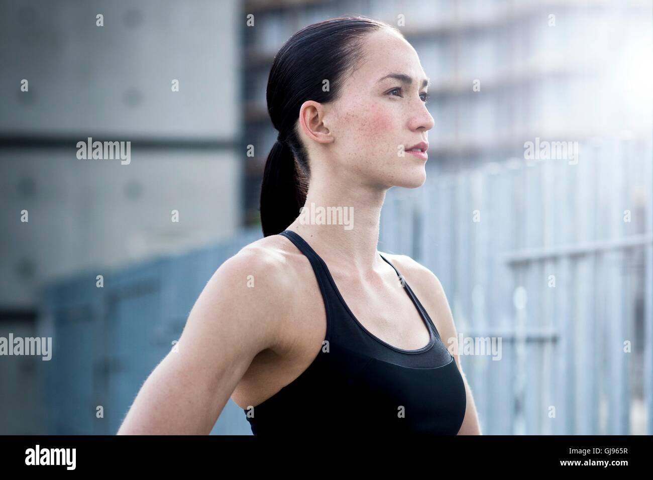 MODEL RELEASED. Young woman in crop top looking away. - Stock Image