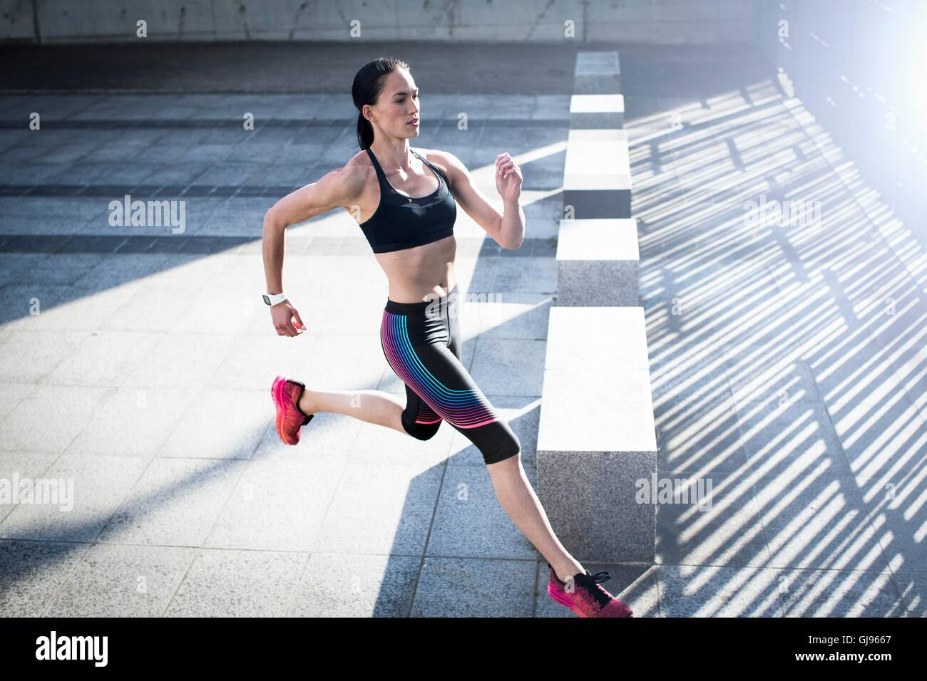 MODEL RELEASED. Young woman running across concrete, high angle. - Stock Image