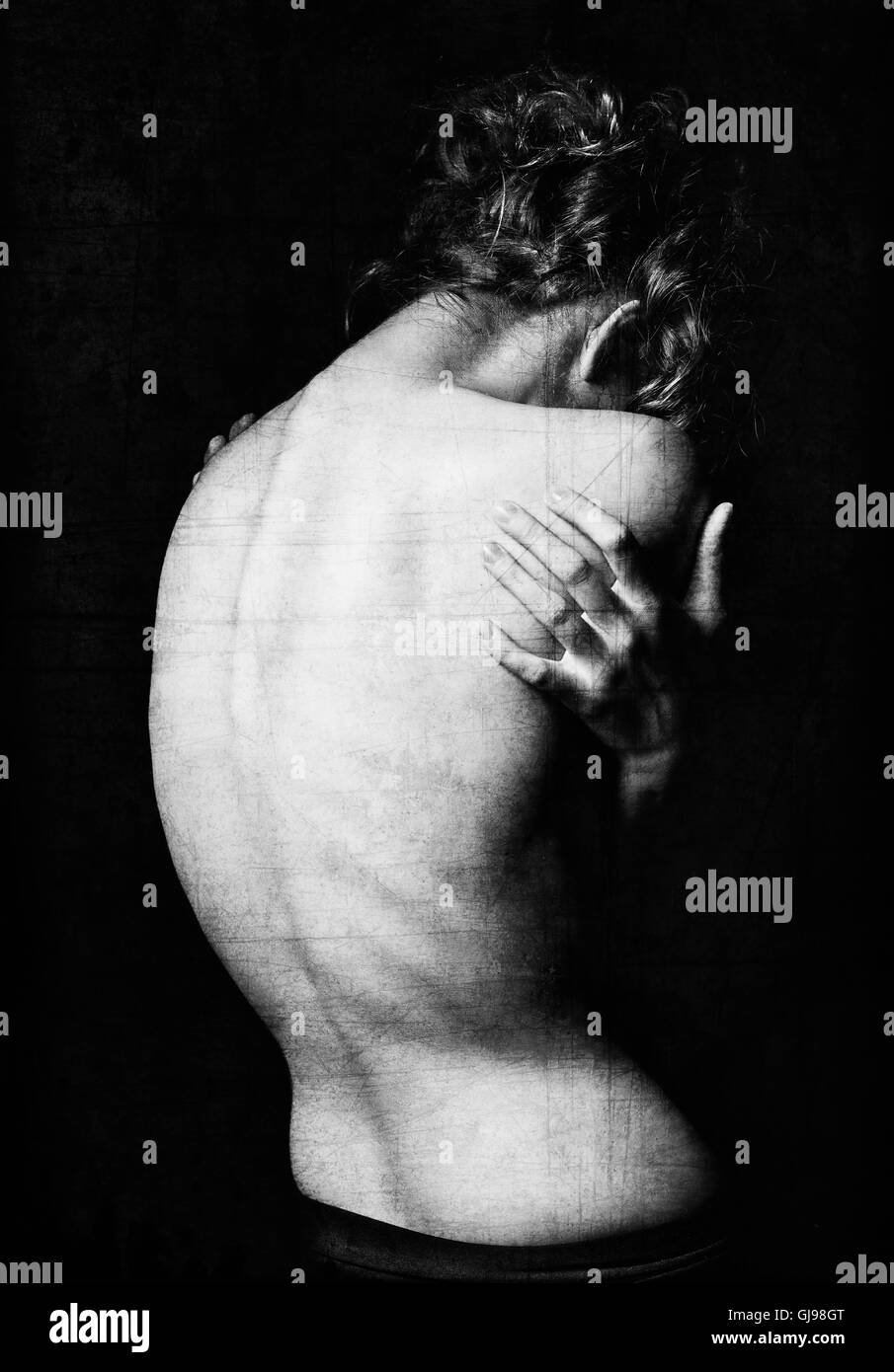 Spooky portrait of a young woman among the dark. Grunge texture effect. Black and white, rear view - Stock Image