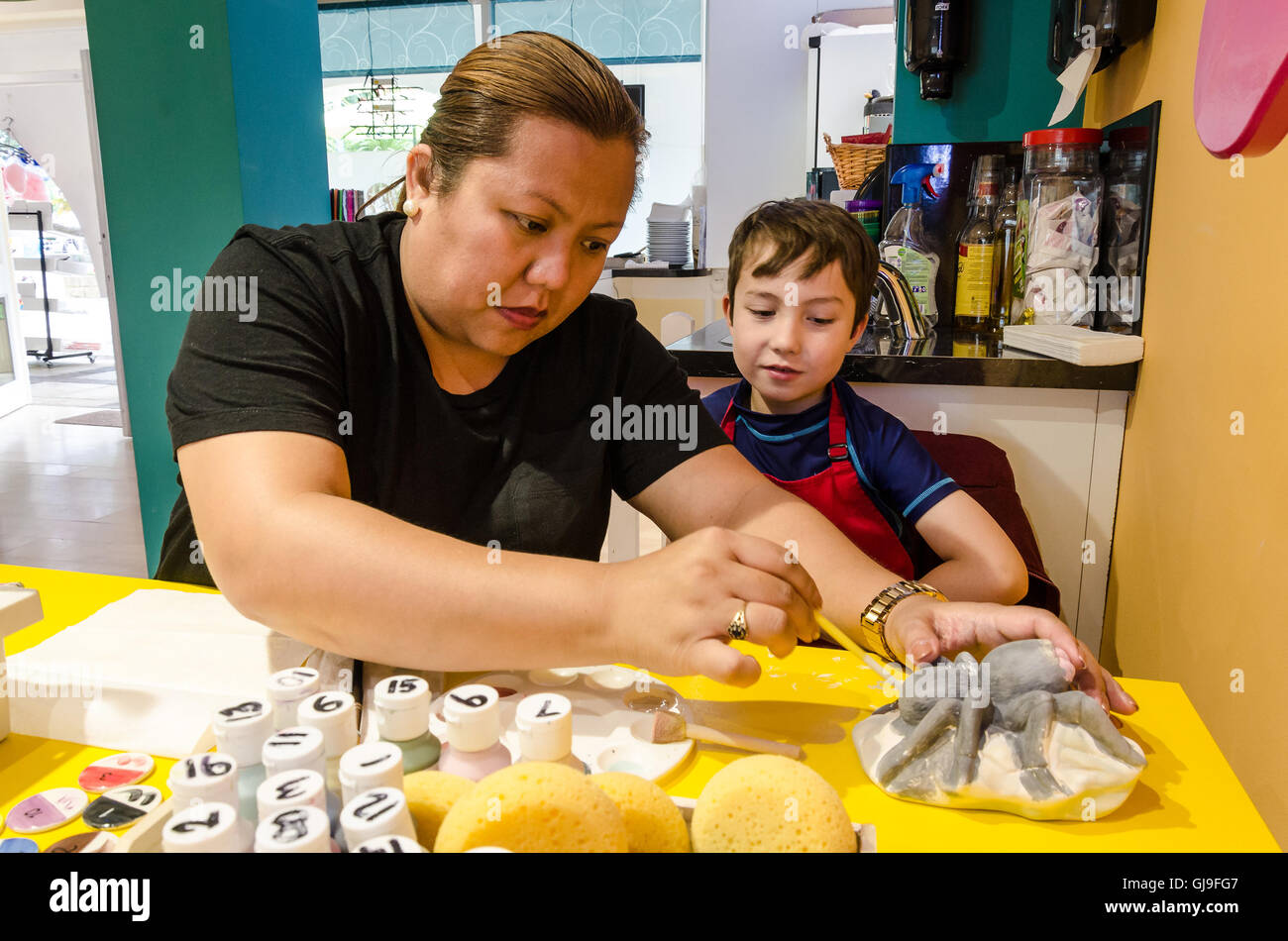 A mother and son paint a pottery spider together. - Stock Image