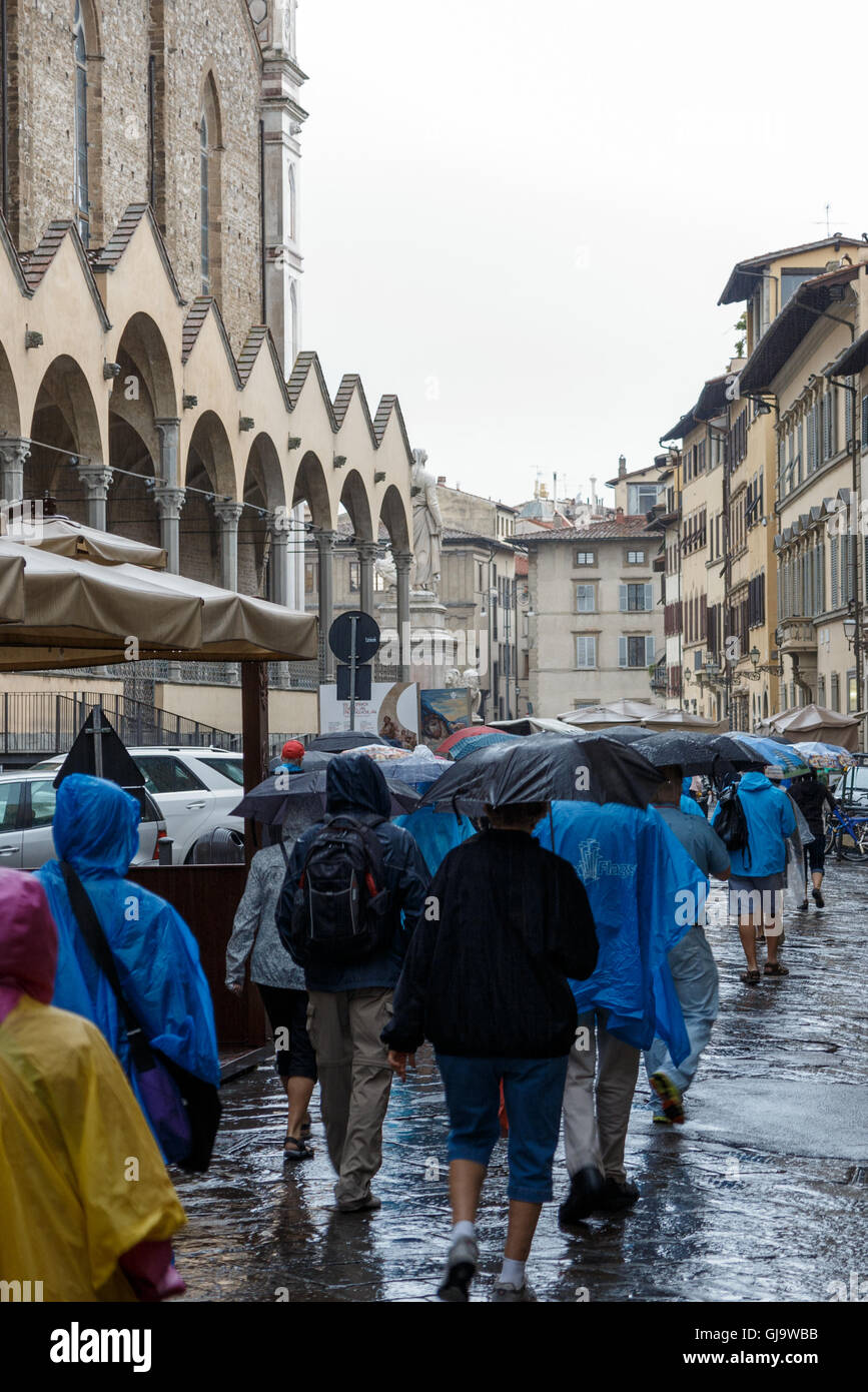 Tourists walk in the rain in Florence, Tuscany, Italy - Stock Image