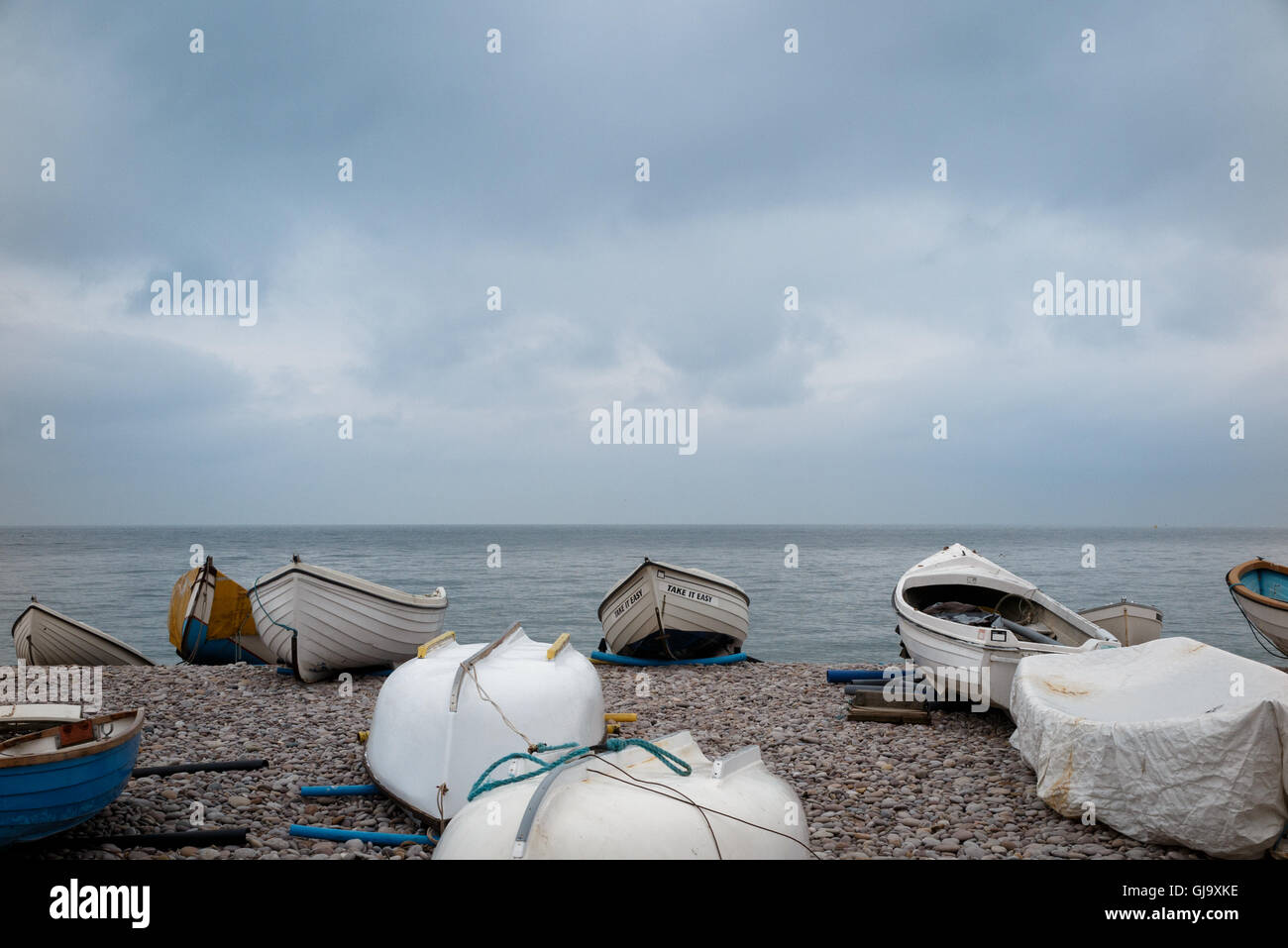 Boats on the beach at Seatown in Devon, winter.  Stormy sky Stock Photo