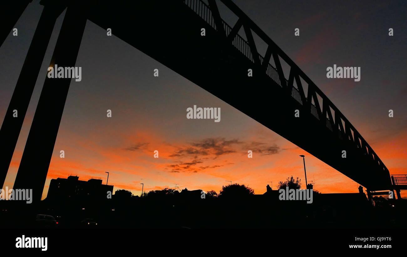 A dramatic sky behind a pedestrian footbridge over the A12 road Wanstead, London E11 Stock Photo