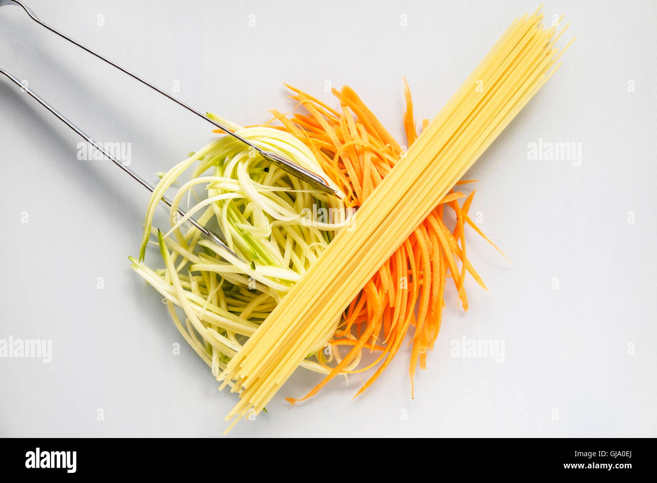 Spiralized zucchini courgette and carrot as a healthy substitute for the spaghetti lying on top with stainless steel - Stock Image