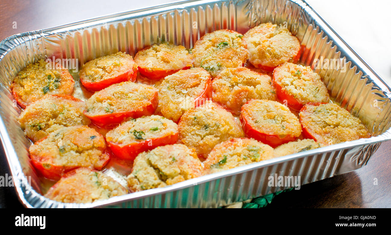 homemade tomatoes au gratin in a baking dish, italian tradition - Stock Image