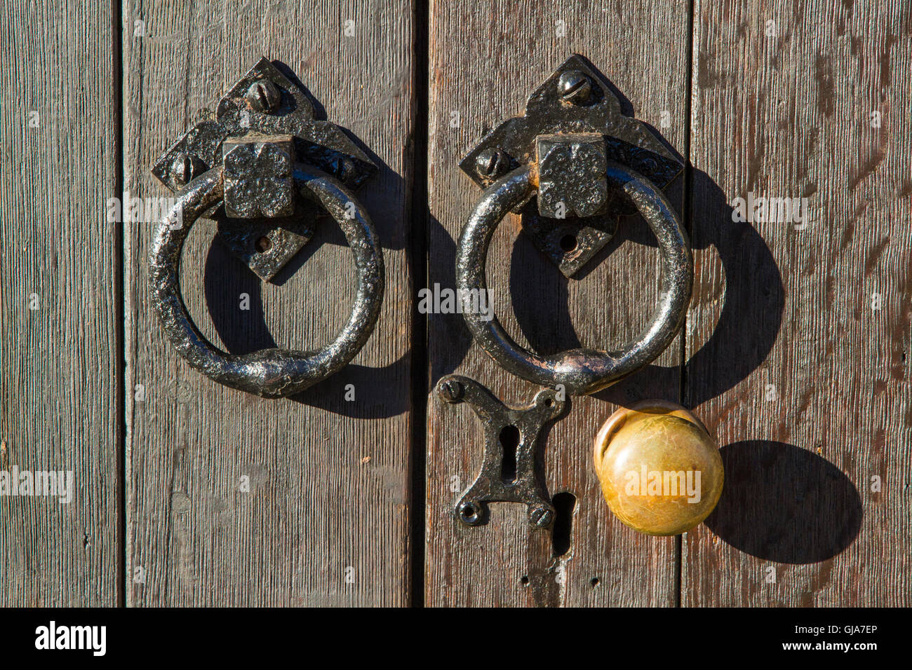Close up of old brass doorknob and iron handles - Stock Image