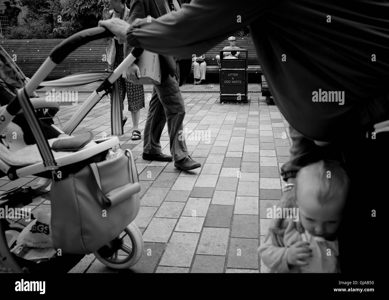 Busy street and man holding walking  toddler close to his legs as though protecting her, keeping her close and safe - Stock Image