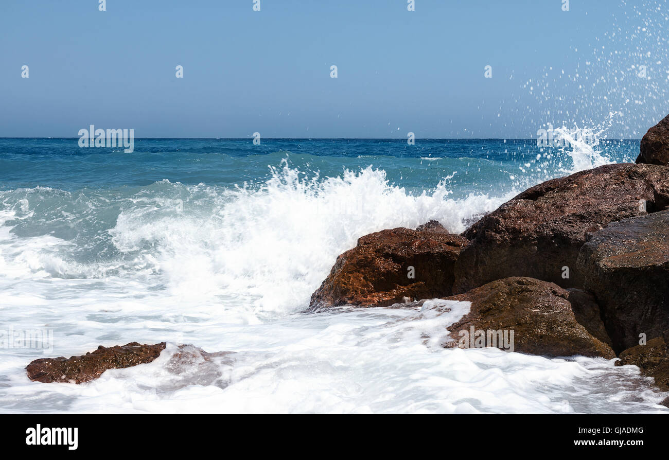 Seascape of white crashing waves on brown sunlight rocks shot for sky to be used as copy space - Stock Image