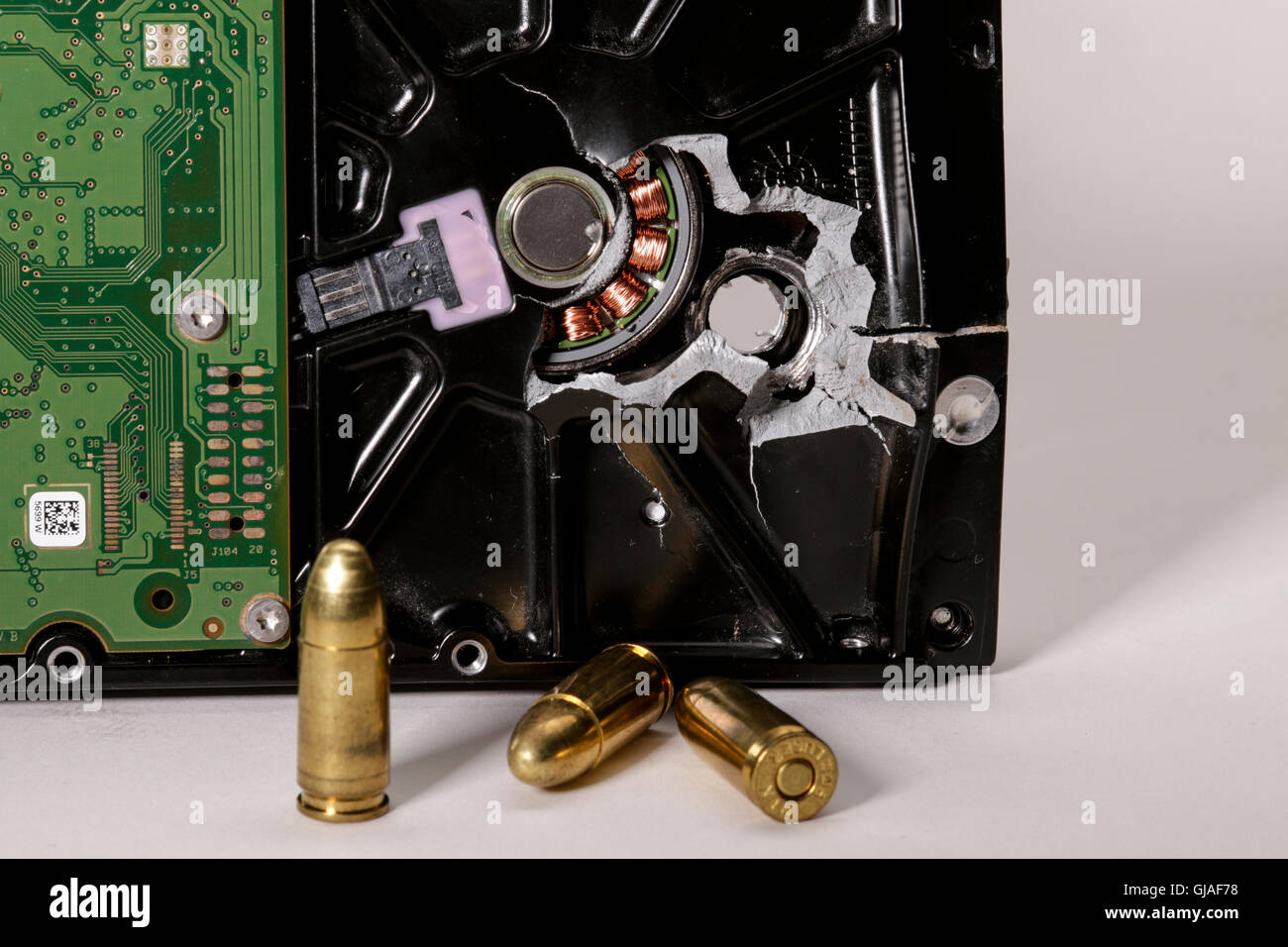Computer hard drive with bullet hole and 9mm bullets. - Stock Image
