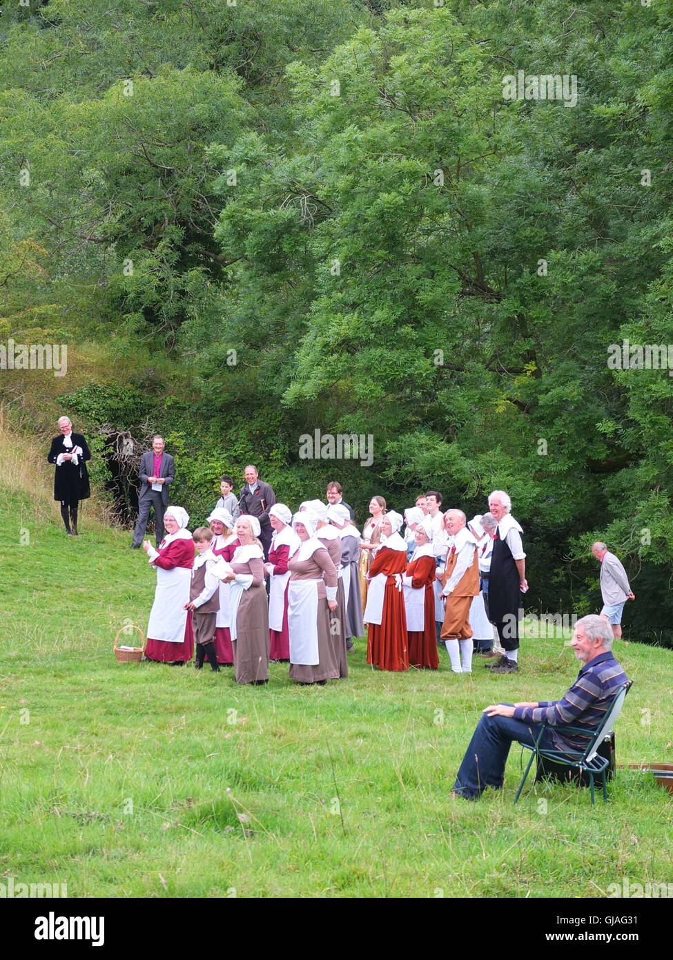 Villagers in costume, the Bishop of Derby and guitarist at the Eyam Plague Commemoration Service at Cucklet Delf - Stock Image