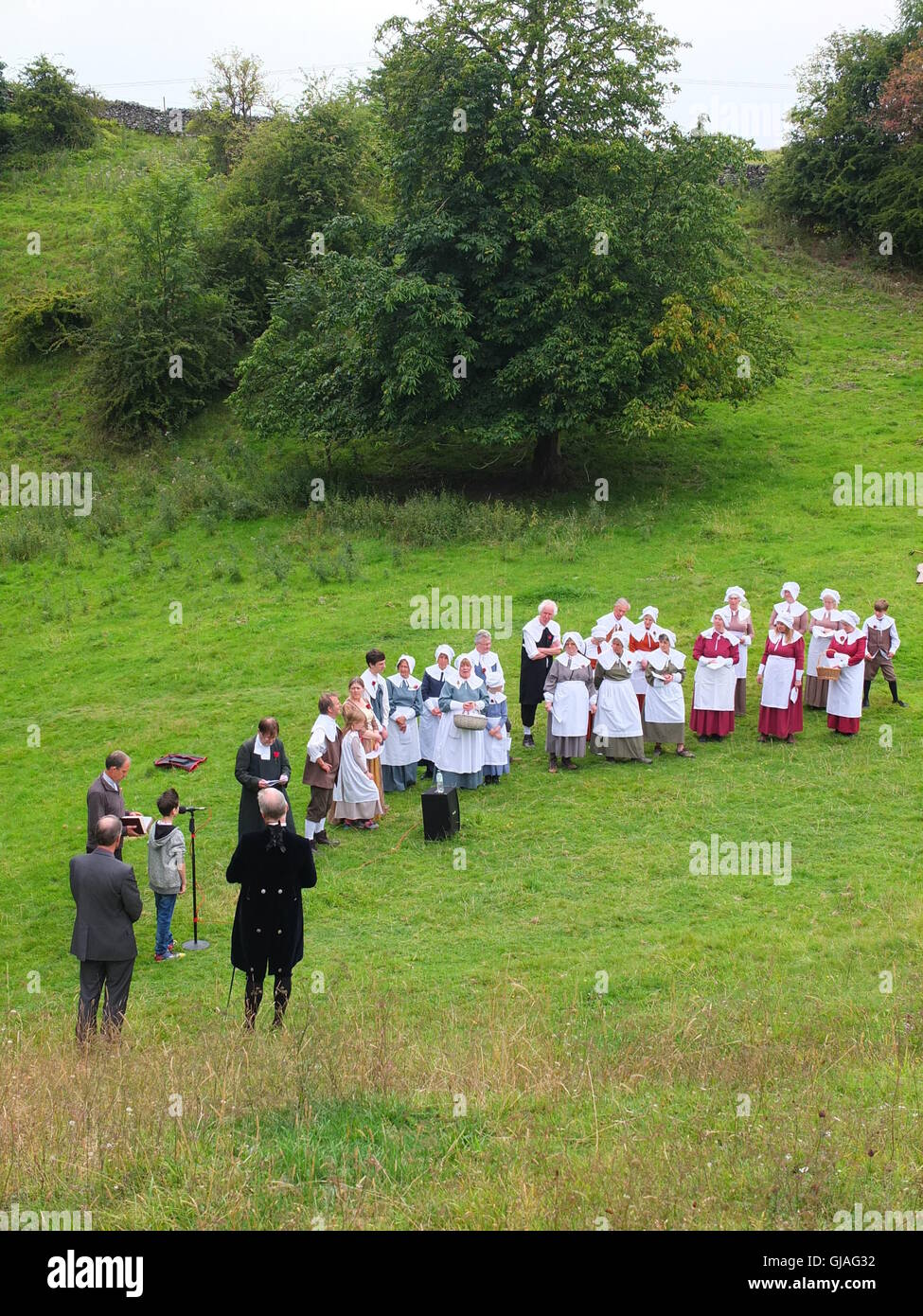 Villagers in costume conduct the Eyam Plague Commemoration Service at Cucklet Delf - Stock Image