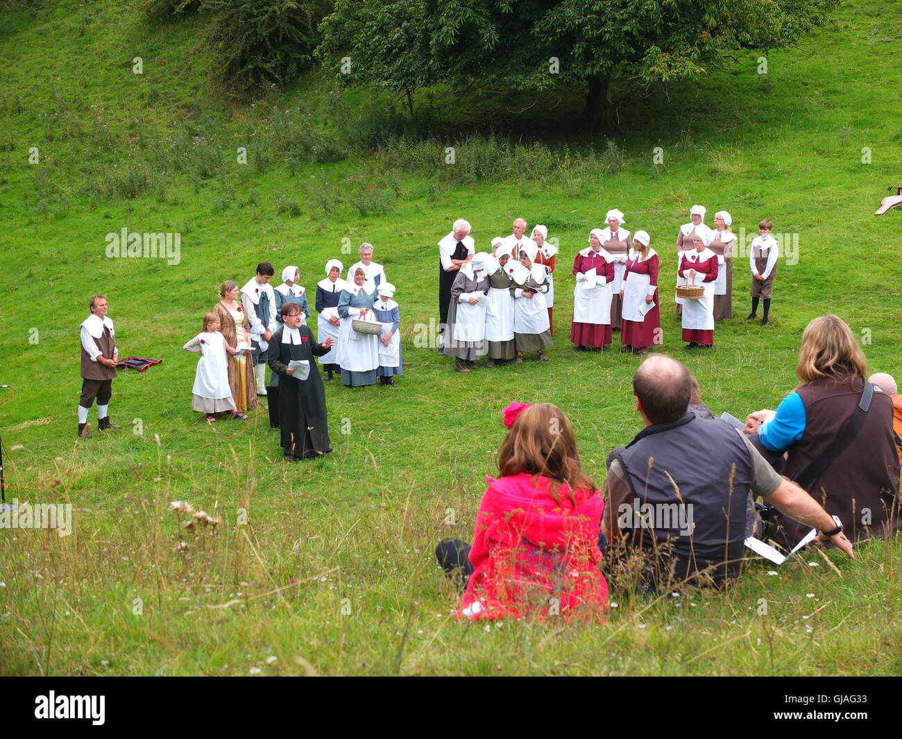 Villagers in costume conduct the Eyam Plague Commemoration Service at Cucklet Delf as attendees watch from the hillside - Stock Image