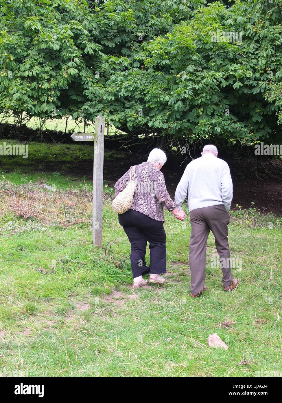 An elderly couple hold hands having attended the annual Plague Commemoration Service at Cucklet Delf, Eyam - Stock Image
