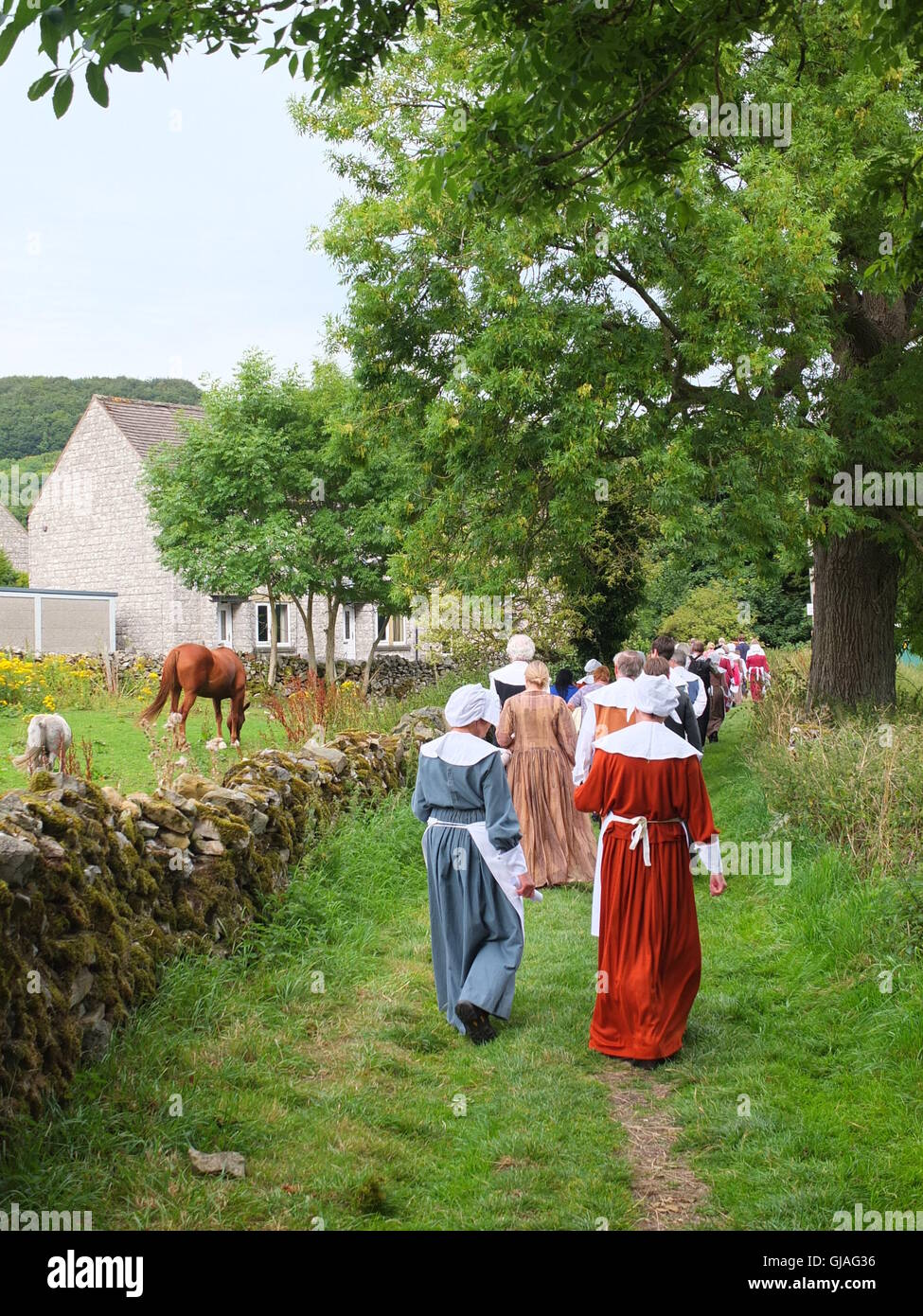 Costumed villagers walk back from Cucklet Delf to the village of Eyam during their annual Plague Commemoration Service - Stock Image
