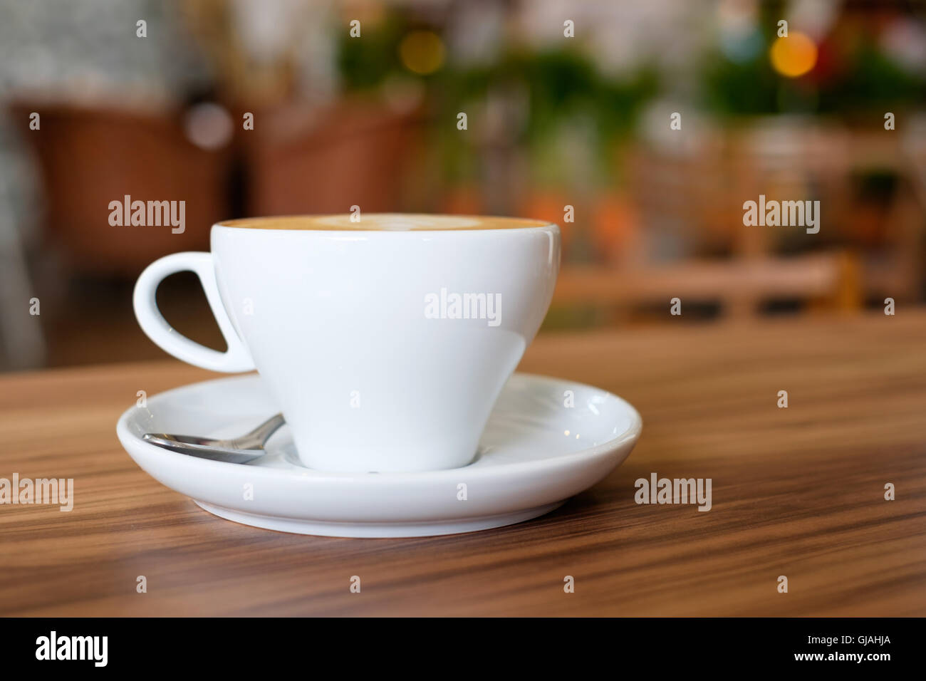 8237aabef29 A white mug cup containing hot coffee on wooden table in cafe. - Stock Image