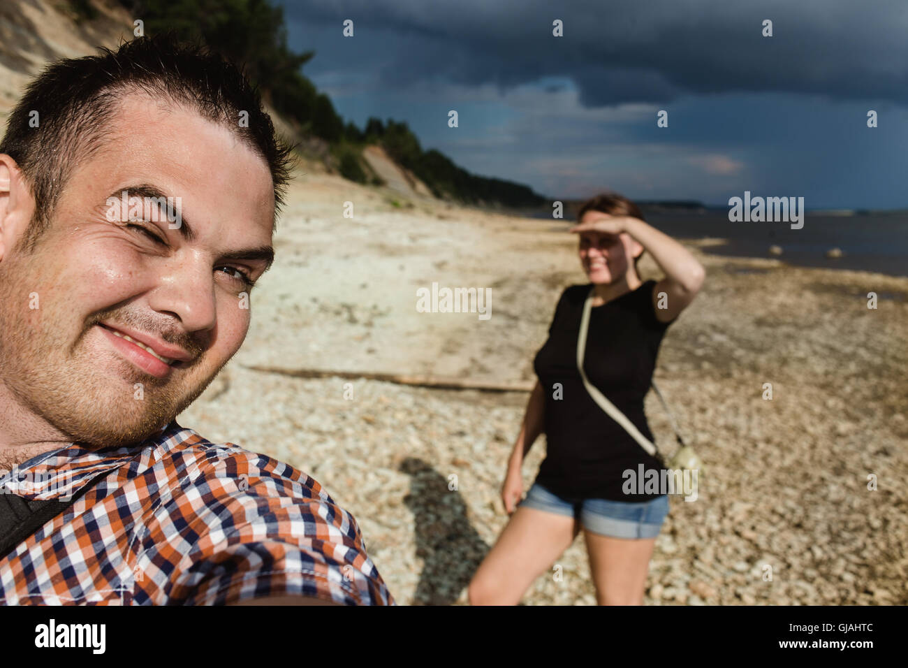 Two hikers taking selfie on forest edge in hot sunny weather - Stock Image