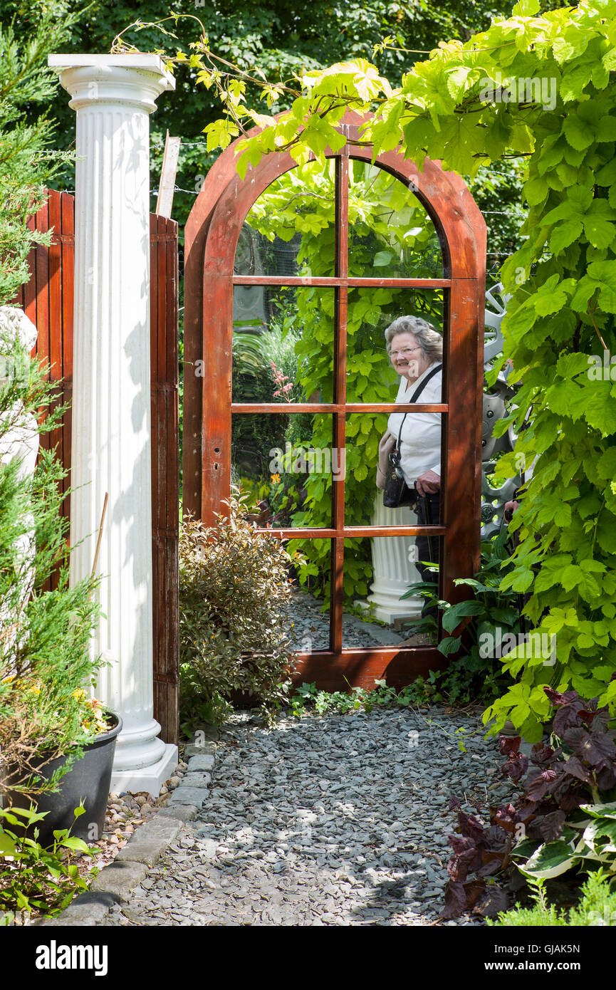 Use of an old mirror in a small community garden giving an illusion of extra space - Stock Image
