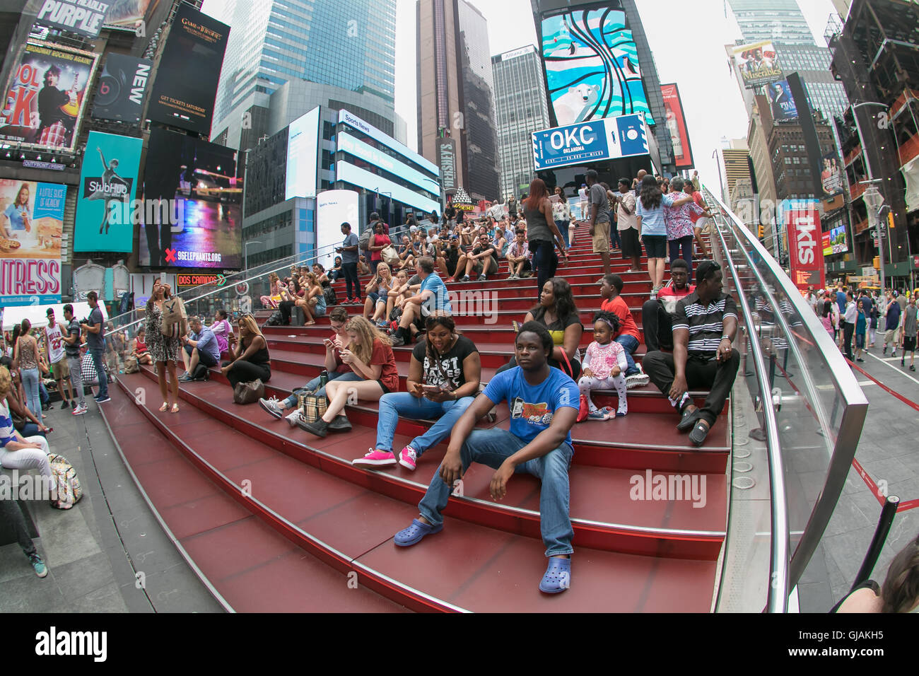 People are sitting on the red steps over a ticket booth on Times Square. - Stock Image